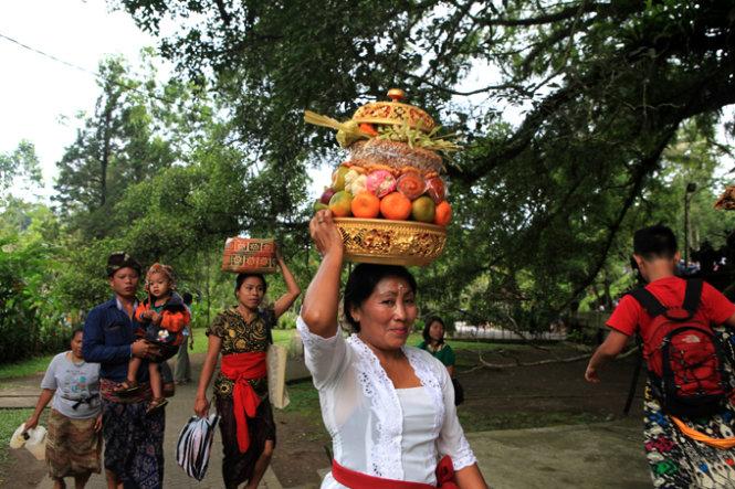 Phụ nữ thường đội những khay lễ đẹp đẽ trên đầu đi bộ vào đền để dâng lễ lên khu thờ chính