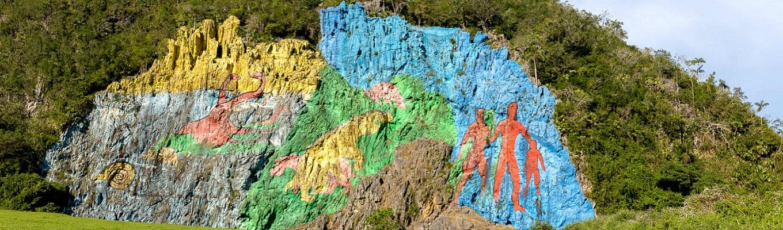 """Bức tranh khổng lồ Mural dela Prehistoria, được vẽ trực tiếp lên vách núi mô tả tiến trình lịch sử của sự sống trên trái đất, do chuyên gia về nghệ thuật """"cổ đại cách tân"""" – Leovigildo González Morillo thực hiện."""